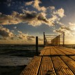 Beautiful sunset over the sea and wooden jetty — Stock Photo #53874847