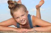 Cheerful blond girl lying on her stomach on the wall and smiling — Stok fotoğraf