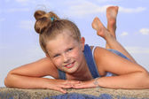 Cheerful little girl lying on her stomach on the wall — Stok fotoğraf