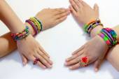 Elastic and colorful rainbow loom bracelet on hands — Stock Photo