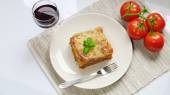 Lasagne on white plate with basi, fresh tomatoes and red wine — Stock Photo