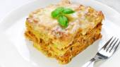 Lasagne with basil on white — Stock Photo