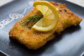 Christmas, fried carp with lemon on dark plate — Stock Photo