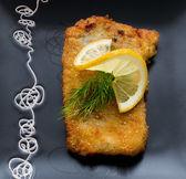 Christmas, fried carp with lemon on black plate — Stock Photo