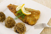 Fried fish with cabbage and mushrooms on white plate — Stock Photo