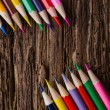 Row of colored drawing pencils on grunge natural wooden background — Stock Photo #80492978