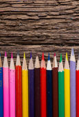 Row of colored drawing pencils on grunge natural wooden background — Stock Photo