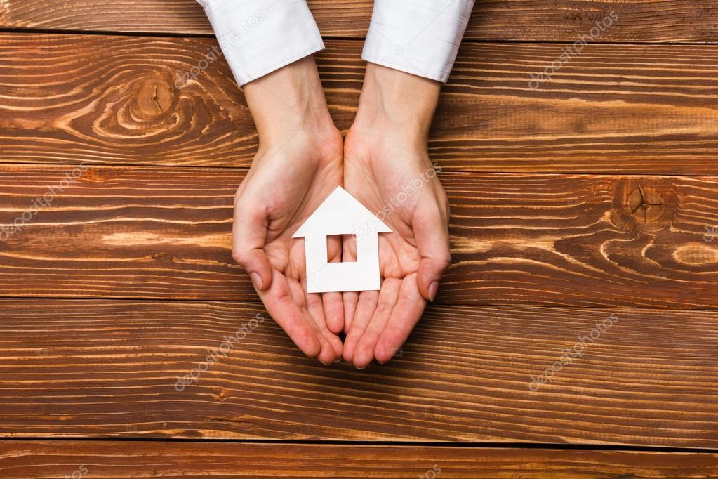figura de manos hplding verde papel casa modelos flechas sobre fondo de madera rstico de grunge concepto de comparacin de bienes races casas precios