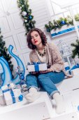 Pretty young girl in jeans and a cardigan with Christmas gifts — Stock Photo