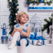 Little smiling pretty girl sitting next to a Christmas tree and — Stockfoto #59475799