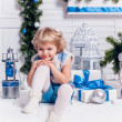 Little smiling pretty girl sitting next to a Christmas tree and — Stockfoto #59475833