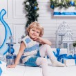 Little smiling pretty girl sitting next to a Christmas tree and — Stockfoto #59475921