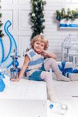 Мало улыбается девушка, сидя рядом с рождественской елки и — Стоковое фото