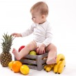 Looking at fruit cute smiling baby on white background among fru — Stock Photo #69101281
