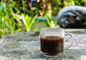 Cup of black coffee on the stone table and Green leaf background — Stock Photo