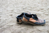 Old sneakers on the sand at the beach. Vintage background. — Fotografia Stock