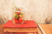 Strawberry jar and a Book on wooden, process color with Vintage — Stock Photo