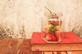 Strawberry jar and a Book on wooden, process color with Vintage — 图库照片
