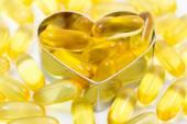 Fish oil pills on heart shape box isolated — Stock Photo
