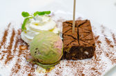 Matcha ice-cream and brownie with wipcream  on white plate — Stock Photo