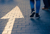 Arrow straight on street with walking people — Stock Photo