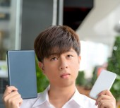 Asian male decide and hesitate to use  smart device — Stock Photo
