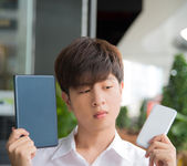 Asian male decide and hesitate to use  smart device which one tablet or smartphone — Stock Photo