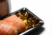 Olio di pesce pillole servite con sushi di salmone isolato — Foto Stock