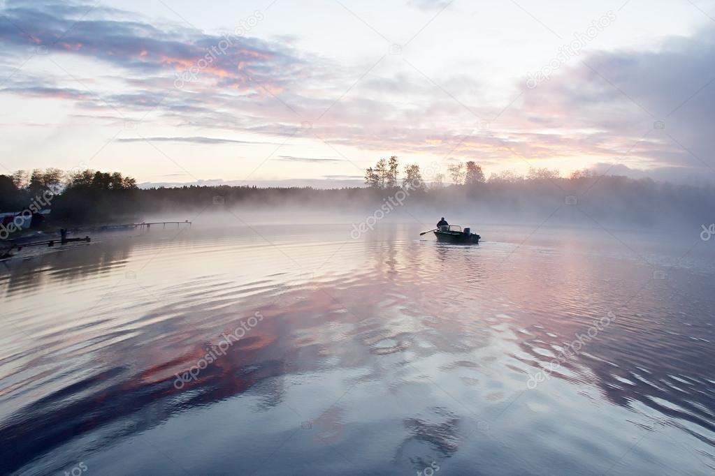 человек в лодке посреди озера