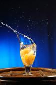 Orange splashing into glass of water — Stock Photo