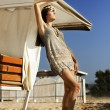 Beautiful young girl short dress standing on sand under an umbrella — Stock Photo #67352781