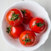 Fresh tomatoes in white bowl on wooden table — Stock Photo
