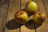 The apples lying on the wooden background. — Stock Photo