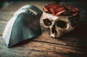 Faded roses in a skull and a visor — Stock Photo