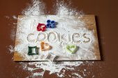 """Cookies"" written in flour sprinkled on a wooden board with cook — Stock Photo"