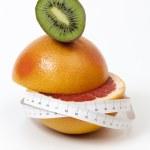 Half sliced red grapefruit and kiwi and tape measure around — Fotografia Stock  #70991277