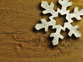 Huge white snowflake and wooden background. — Stockfoto