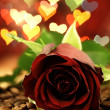 Red rose on a wooden table and hearts. — Stock Photo #60714893