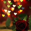 Red rose on a wooden table and hearts. — Stock Photo #60714943