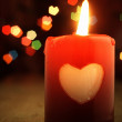 Red candle on the table and shiny hearts in background. — Stock Photo #60715231