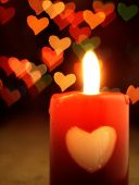 Red candle on the table and shiny hearts in background. — Stock Photo