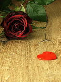 Red rose and red heart on a wooden table. — Стоковое фото
