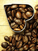 Heart and Coffee beans close-up on wooden, oak table. — Stock Photo