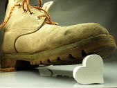 Heavy military boot trampling heart. — Stock Photo