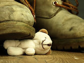 Teddy bear crushed by a heavy, old military boot. — Stock Photo