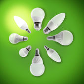 Glowing LED energy saving bulb in a hand on a green background — Stock Photo