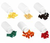 A set of pills spilling out of white plastic medicine bottle. — Stock Photo