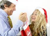 Mature man offering a Christmas gift to his wife — Foto Stock