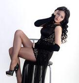 Female model in evening dress is sitting — Stockfoto