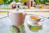 Cup of tea and teapot on glass table — Stock Photo